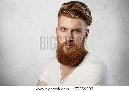 Headshot Of Stylish Young Student With Thick Red Beard Wearing T-shirt Having Rest Indoors After Lec