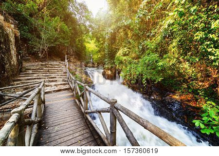 Wooden Boardwalk And Stone Stairs Leading Along Scenic River