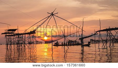 Sunrise at Pak Pra lakePattalungThailand. Silhouette of traditional fishing method using a bamboo square dip netsun in net