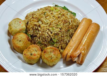 fried rice in black soy sauce and pork sausage with chicken jock on dish