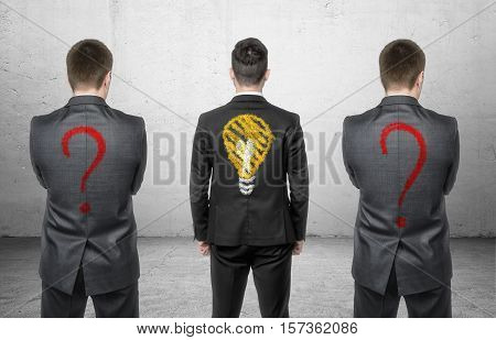 Three businessmen standing with drawing of light bulb and question marks on his back. Business and management. Solving problems. Having ideas.
