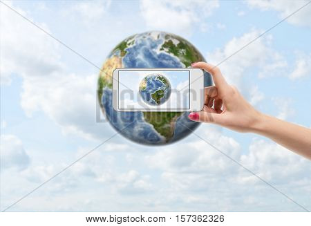 A female hand with a smartphone taking a photograph of the Earth. Environment and sustainability. Ecological problems. Climate issues. Saving the planet. Elements of this image are furnished by NASA.