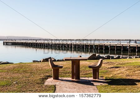 Picnic table and chairs at Chula Vista Bayfront park with fishing pier in the background.