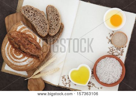 Rustic rye bread  loaf with baking ingredients and wheat sheaths with loose grain on natural hemp notebook.
