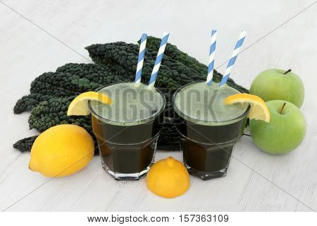 Kale health drink with fresh vegetable leaves, lemon and apple fruit over distressed white wood background. High in vitamins and antioxidants.