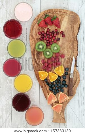 Fresh fruit on an olive wood board with corresponding health smoothie and juice drinks. Strawberry, cranberry, kiwi, raspberry, orange, blueberry and grapefruit, top to bottom.