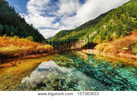 Crystal Clear Water Of River Among Mountains In Autumn