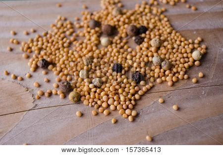 Spicy mustard seeds in a wooden background. Organic mustard seeds on brown table. Assorted spices for cooking on the wood surface.