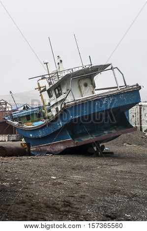 fishing boat lies on the beach in anticipation of the opening of navigation in the Chukotka region in Russia