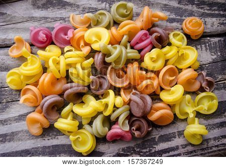 Heap of colored italian pasta on old woden desk. Bunch of raw pasta isolated on gray striped background.