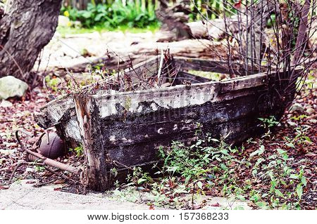 Last place of old broken boat in autumn garden. Vintage style.