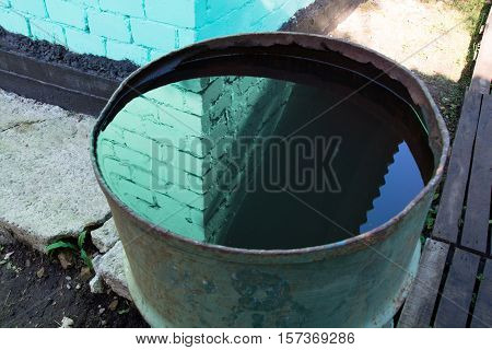 Water surface in the barrel is reflecting a wall corner. Wall of the green brick house.