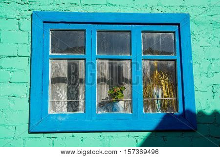 Vintage window located on a green wall. Wooden window's frame.