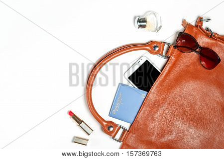 Female bag things - leather bag, makeup items, smartphone, perfume, silk scarf, isolated on white background