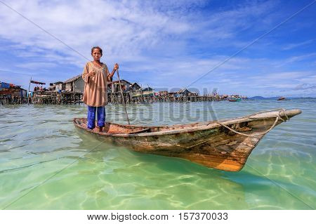 Semporna,Sabah-Sept 11,2016:Sea Gypsy girl on a boat on 10th Sept 2016 at Semporna,Sabah.The gypsy kid are given a net & taught to catch fish,octopus & lobsters off their unique handmade boats