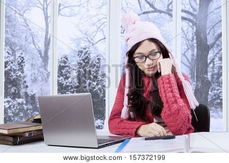 Female high school student studying at home with laptop and book on the table shot near the window