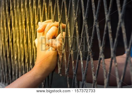 Hands of the man and woman on a steel lattice close up process in soft orange sun light style