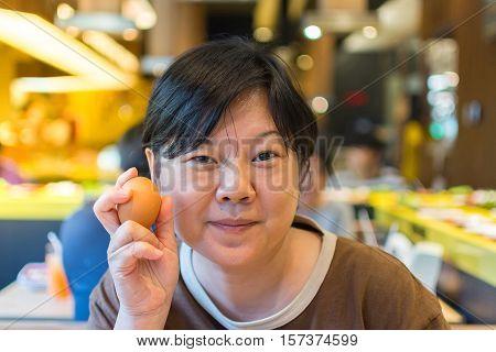 Asia Woman Holding A Egg In Bbq. Yakiniku Grill Buffet Restaurant