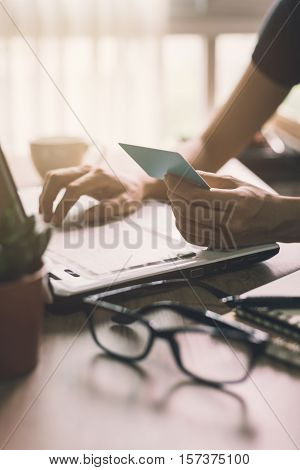 girl holding credit card and typing on laptop Vintage tone