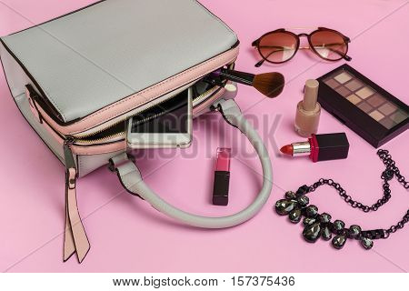 Fashion woman handbag with cellphone makeup and accessories isolated on pink background Top view