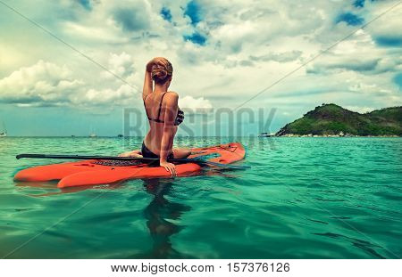 Young slim girl  sitting on   paddle board in turquoise sea , SUP, Tropical Blue Ocean . Thailand ,water sports , active lifestyle
