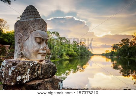 Stone Face Asura And Sunset Over Moat. Angkor Thom, Cambodia