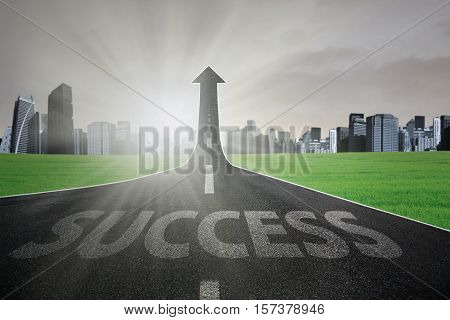 Empty road with a success text turning into arrow upward to the sky symbolizing the way to gain success