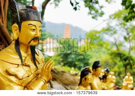 Closeup View Of Golden Buddha Statue On Background Of A Red Pagoda And Forest In Hong Kong