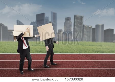 Image of two businessmen with cardboard on their head and walking on the track