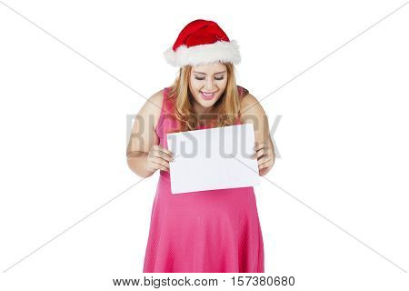 Overweight woman in santa hat holding blank board for advertisement isolated on white background
