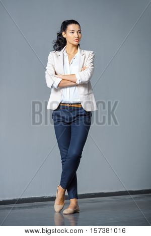Beautiful brunette business woman in suit standing outdoors against gray background and looking away in full lenght. Copy space