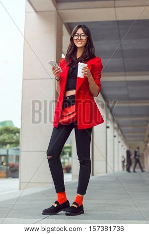 Young pretty businesswoman texting outdoors. Beautiful young stylish asian woman in full lenght in red casual suite and glasses with phone and cup of coffee smiling and looking at camera against street background
