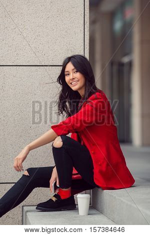 Happy asian businesswoman smiling in the city. Happy lovely and beautiful mixed race Asian Caucasian young woman in casual red suite outdoor sitting on steps of building with coffee cup. Next generation