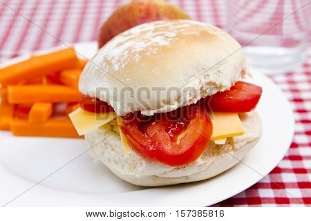 Cheese and tomato roll with apple, crisps and a glass of water