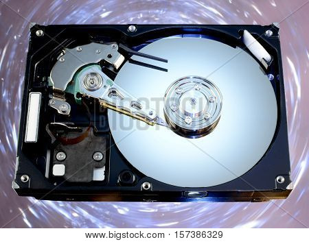 Disassembled hard drive from the computer with a mirror effect. Computer Part on a colorful background