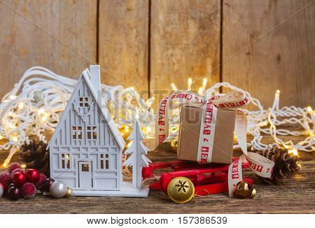 House and gift box on sledge with christmas lights on wooden background