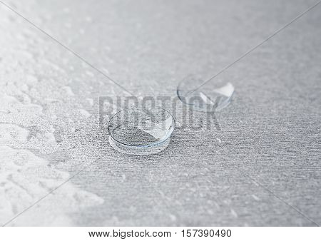 Pair of contact lenses and drops of solution on grey background, close up view