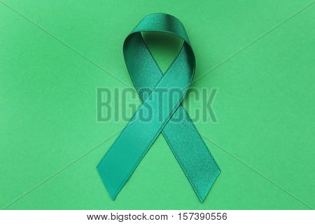 Green ribbon on color background. Mitochondrial diseases and kidney cancer concept