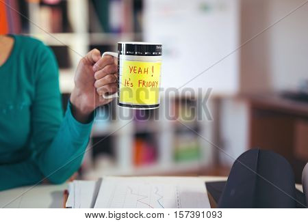 Woman holding a cup of coffee with a motivational message: Yeah! It's Friday!
