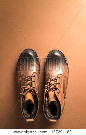 Brown leather boots over brown backgroundabove view with copy space for text