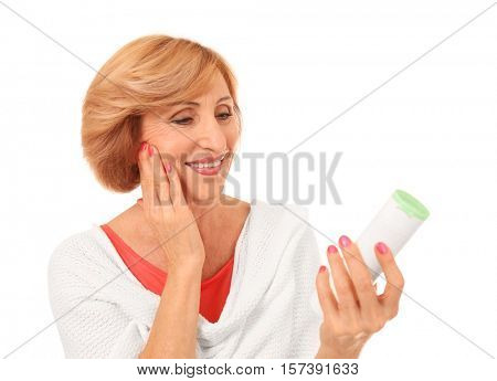 Portrait of senior woman holding bottle of anti-aging lotion, isolated on white
