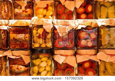 many jars with preserved italian food with tomatoes and garlic and sardines in oil