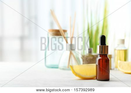 Beautiful spa composition with lemon essential oil on white wooden table, closeup