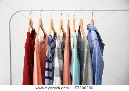 Hangers with different female clothes on light background