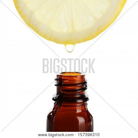 Slice of lemon with glass bottle and essential oil on white background