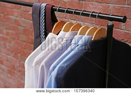 Hangers with male shirts and ties on clothes rail, closeup