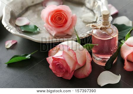 Bottle of aroma oil with roses on table