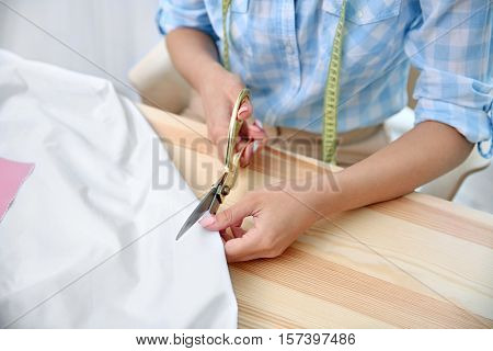 Young dressmaker cutting cloth, close up