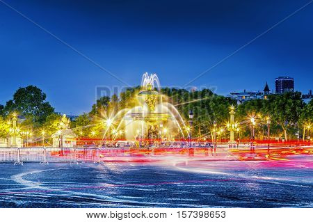 Fountain at the Place de la Concorde in Paris by night, France. Night scene. Traffic tracers from cars at long exposure.