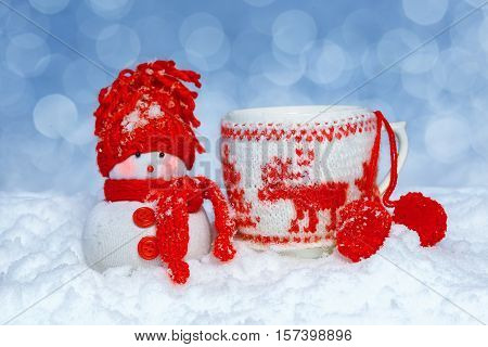 Snowman wearing a colored hat and scarf standing near mugs in red knitted mitten on snowy blurred background. Beautiful Christmas decor